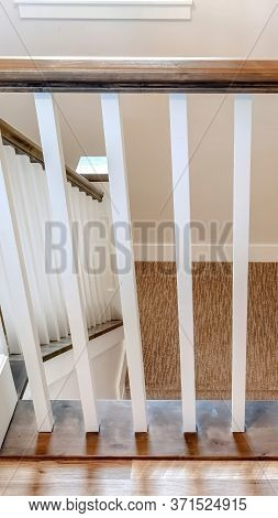 Vertical Frame U Shaped Stairway Of Home With Brwon Handrail Supported By White Balusters