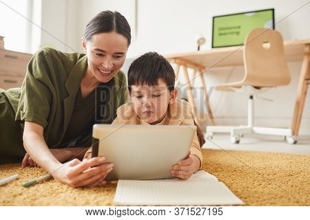 Portrait Of Smiling Young Mother Laying On Floor With Cute Son Using Difital Tablet, Copy Space