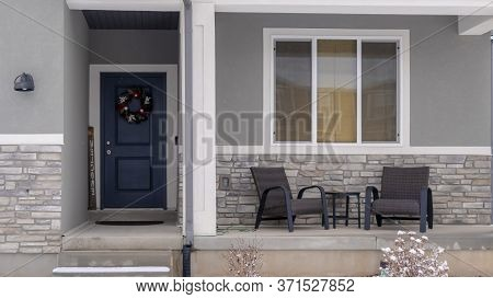 Panorama Crop Home Facade With Gable Roof Front Porch And Door With Wreath In Winter