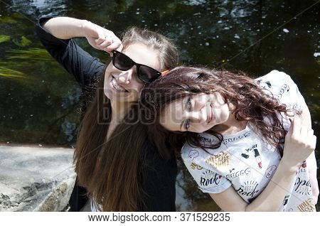 Happy Girls Relax On Stony Coast. Lake Or River Water Pond. Beautiful Places. Travel With Best Frien