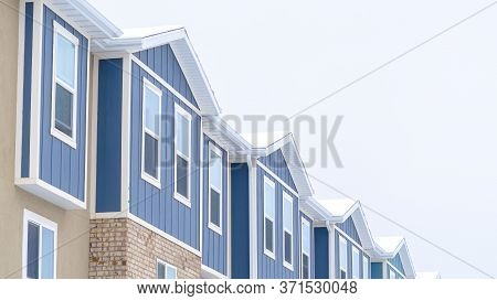 Panorama Snowy Gable Roofs At The Facade Of Townhome With Brick Wall And Vertical Siding