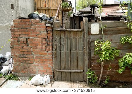 Background Old Wooden Door, Brick Wall And Trash Bags. Village Slums