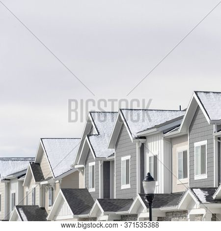 Square Frame Facade Of Townhouses In South Jordan Utah With Snowy Gable Roofs In Winter