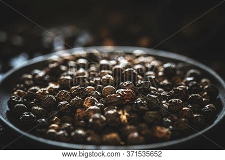 Pile Of Black Peppercorns In Black Plate, Close Up Shot