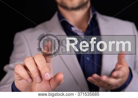 Businessman On A Black Background Pressing A Reform Concept Button.
