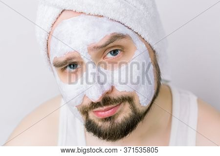 Close Up Of Face Of Handsome Serious Bearded Man With White Towel On His Head And Mud Cleansing Mask