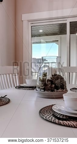 Vertical Dining Table With Chairs And Tableware Arranged Around A Decorative Centerpiece