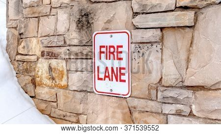 Panorama Fire Lane Sign On Stone Retaining Wall Amid Thick Fresh Snow On A Hill In Winter