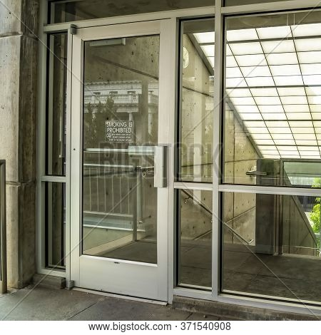Square Crop Glass Door And Wall With View Of Slanted Frosted Roof Over Stairway Of Building
