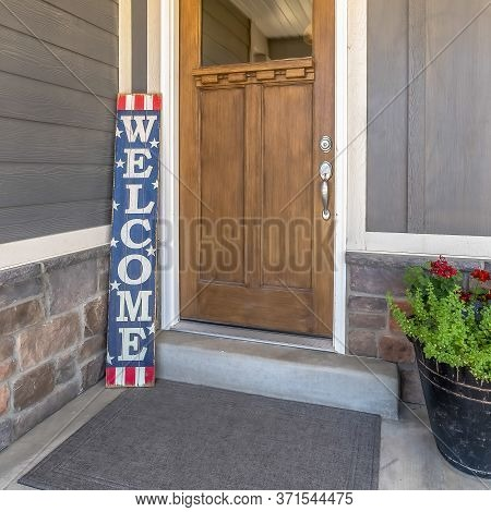 Square Brown Front Door With Glass Pane And Welcome Sign Against Gray And Stone Wall