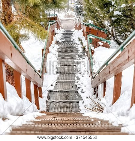 Square Frame Metal Grate Tread Stairs On Snowy Hill Going Down To A Road Viewed In Winter