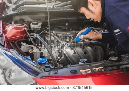 Man Mechanic Inspection Shine A Torch Car Engine Checking Bug In Engine From Application Smartphone.