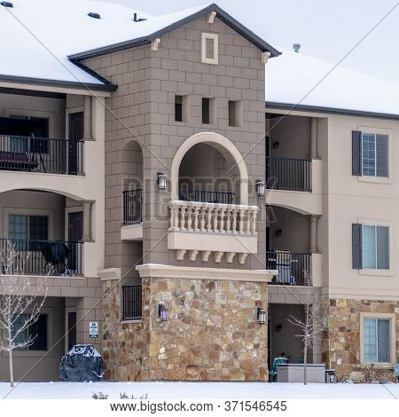 Square Beautiful Apartment With Front Gable Roof And Arched Balcony Viewed In Winter