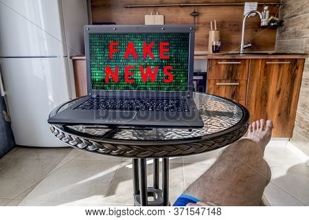 A Man Is Sitting In Front Of A Laptop With Fake News On The Screen At Home