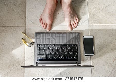 Male Bare Feet Stand In Front Of A Laptop And Smartphone Lying On The Floor At Home.