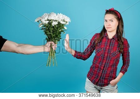 A Country Girl In A Red Plaid Shirt Refuses A Gift In The Form Of Flowers. A Man Gives Her White Chr