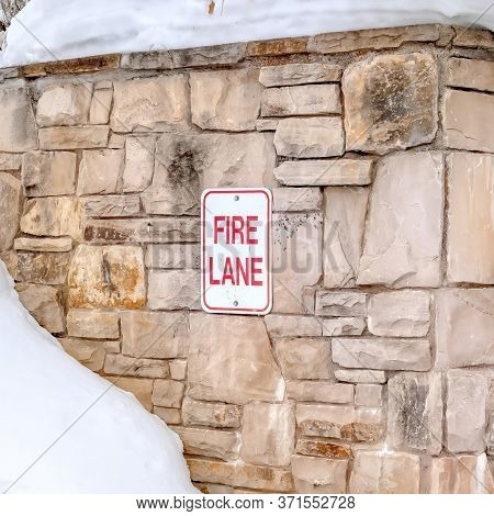 Square Stone Retaining Wall With Fire Lane Sign On A Hill With Thick Snow In Winter