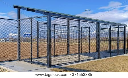 Panorama Crop Baseball Field Dugout With Slanted Roof And Chain Link Fence On A Sunny Day