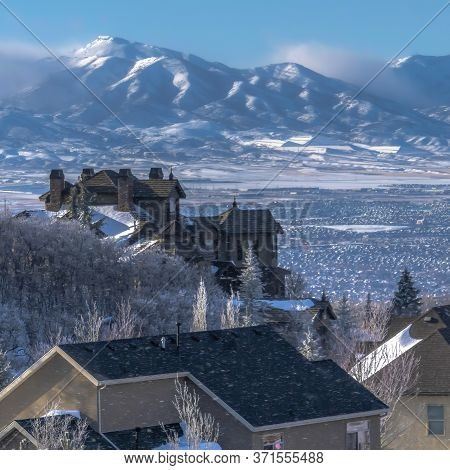 Square Frame Snow Falling On Homes With Sweeping View Of Valley And Towering Wasatch Mountain