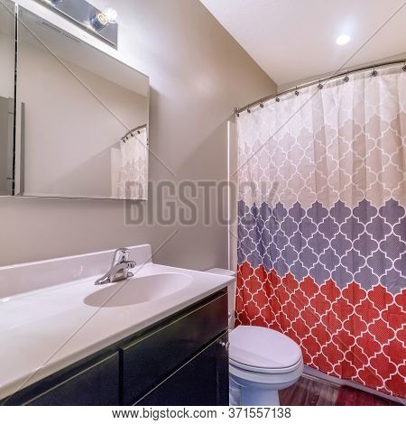 Square Home Bathroom With Toilet Vanity Area And Bathtub Conceled By Colorful Curtain