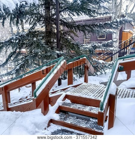 Square Stairs With Green Handrails And Grate Metal Treads Built On Hill With Fresh Snow