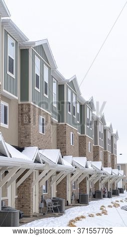 Vertical Townhome Facade With Snowy Gabled Roof At The Entrance In Winter