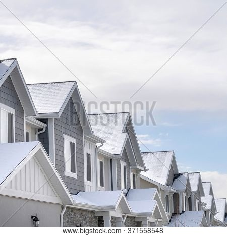 Square Frame Facade Of Snowy Townhouses In South Jordan Utah Against Cloudy Sky In Winter