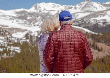 Family Admires The Mountain Scenery (rear View). Man And Woman Traveling In The Mountains In Summer.