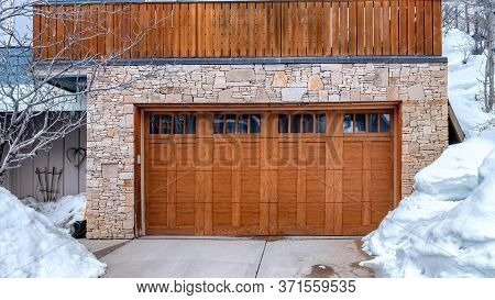 Panorama Brown Wooden Glass Paned Garage Door Against Stone Wall Under Balcony Of Home