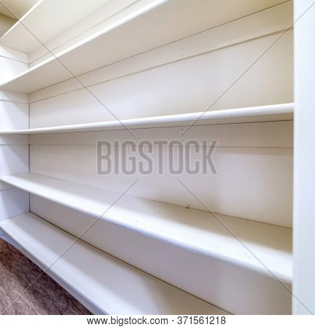 Square Crop Small Walk In Closet With Empty Long Cabinet Shelves Under Slanted Ceiling