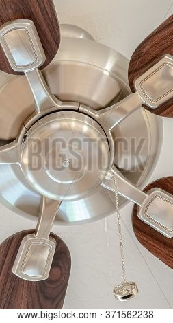 Vertical Ceiling Fan With Wooden Blades And Lights Mounted On The Ceiling Of A Home