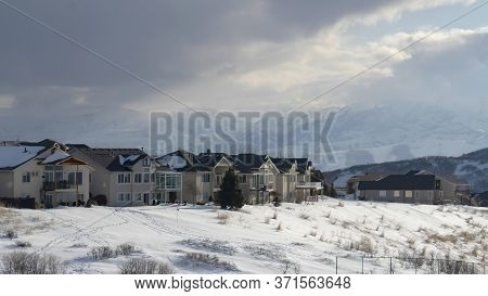 Panorama Crop Homes On Snowy Terrain Ovelooking Wasatch Mountain Peak And Dark Overcast Sky