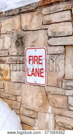 Vertical Frame Fire Lane Sign On Stone Retaining Wall Amid Thick Fresh Snow On A Hill In Winter