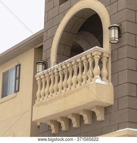 Square Exterior Of Apartment With Moulded White Balustrade On The Arched Balcony