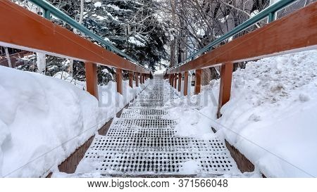 Panorama Grate Tread Stairs With Wood And Metal Hansrail Against Snowy Hill In Winter