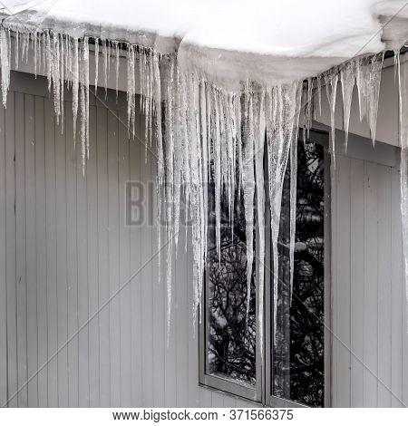 Square Sharp Spiked Icicles On Roof With Snow Against Snowy Hill Landscape In Winter
