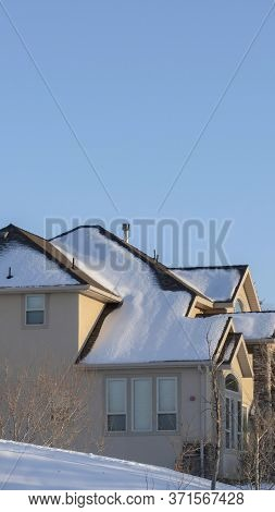 Vertical Frame Sunny Day In Wasatch Mountains With Houses On The Snowy Terrain In Winter