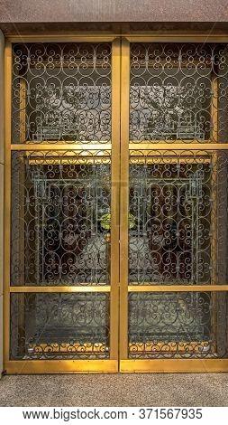 Vertical Crop Decorative Wrought Iron Door With Gold Frames In Front Of Glass Door Of Building