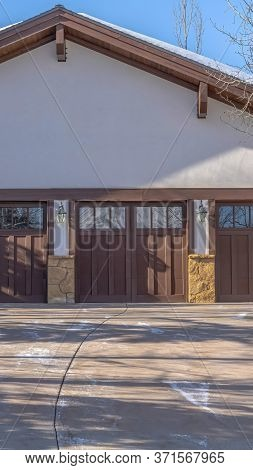 Vertical Crop Driveway Leading To Three Wooden Garage Doors With Glass Panes In Park City Utah
