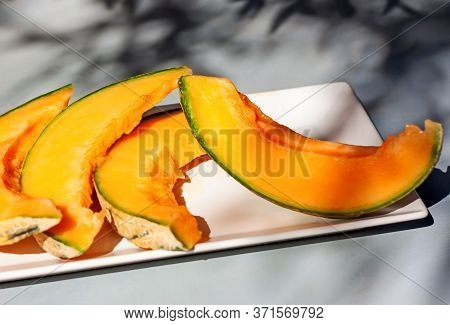 Honey Melon Or Cantaloupe Cucumis Melo. Sliced Of Japanese Melon On White Plate With Shadows. Summer