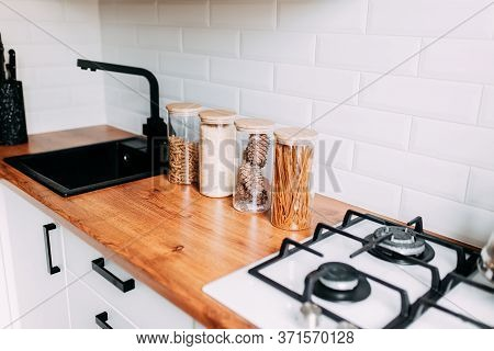 Glass Jars With Grain In Kitchen. Bright Kitchen Interior. White Modern Dining Room. Wooden Complete