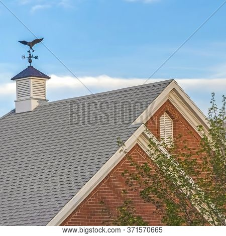 Square Frame Weather Vane And Vent On Top Of The Gray Gable Roof Of Home Against Blue Sky