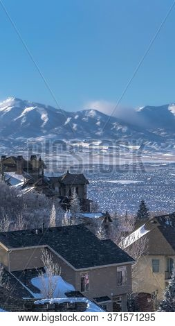 Vertical Frame Snow Falling On Homes With Sweeping View Of Valley And Towering Wasatch Mountain