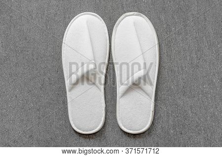 Top View Two Pairs Of New Soft White Slipper In The Hotel On Gray Ceramic Floor. Four White Slipper,