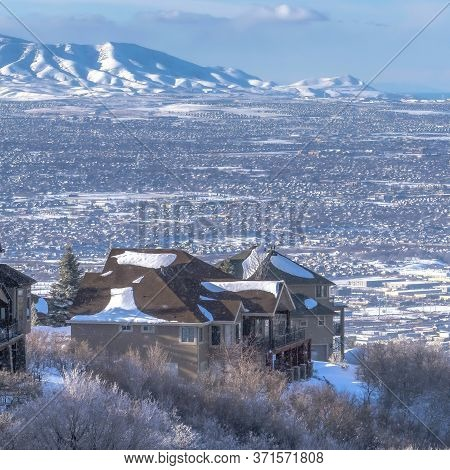 Square Crop Snow Falling On Wasatch Mountains With Homes On Frosted Terrain In Winter