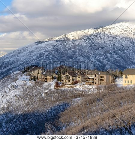 Square Crop Homes On Snowy Terrain Of Wasatch Mountains With Sunlit Peak In The Background