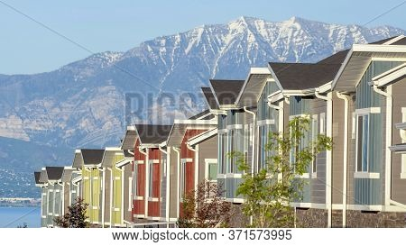 Panorama Crop Townhouses Exterior With Scenic Lake And Snowy Steep Mountain Background