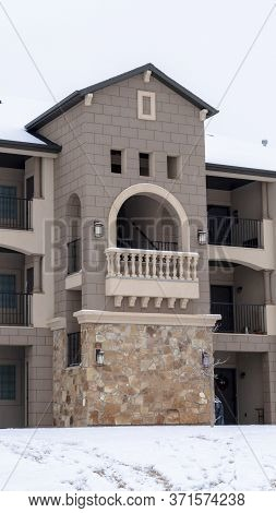 Vertical Facade Of Apartments With Gabled Arched Balcony At The Center Of The Building