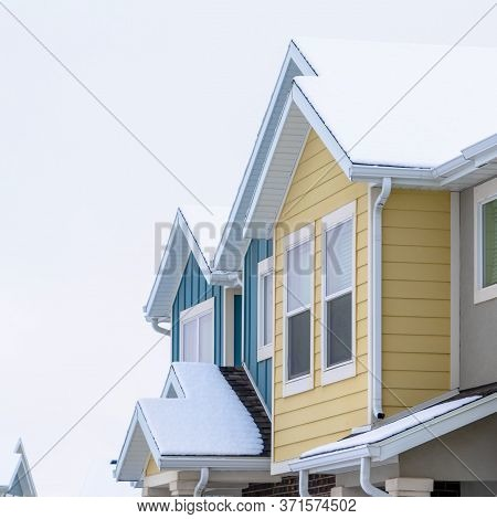 Square Frame Townhome Exterior With Snowy Gable Valley Roof Against Overcast Sky In Winter