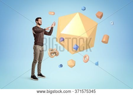 Young Man Standing And Trying To Manipulate A Huge Yellow Icosahedron Floating In Air With Lots Of O